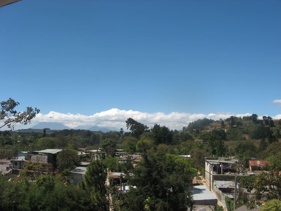 Vista Frontal, al fondo Semi cubiertos por las nubes, estan el Volcan de Agua, Volcan de Fuego y Vocan de Acatenango.