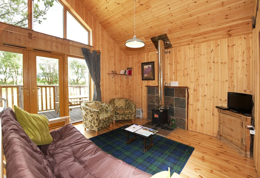 Living area with vaulted ceiling and wood burner