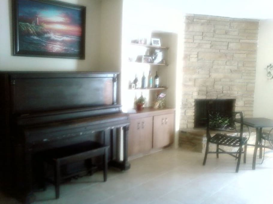 Foyer area with piano and fireplace.