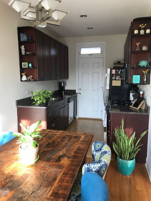 Fully stocked kitchen with dishwasher, stove, microwave, and granite counters.