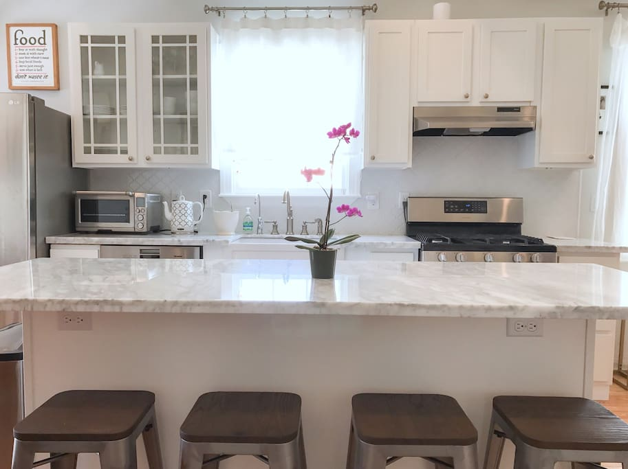 Kitchen features a marble island with bar stools for easy dining.