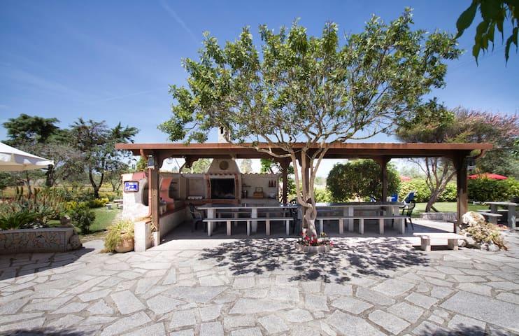 La grande veranda con tavolo in granito nel patio davanti al casolare