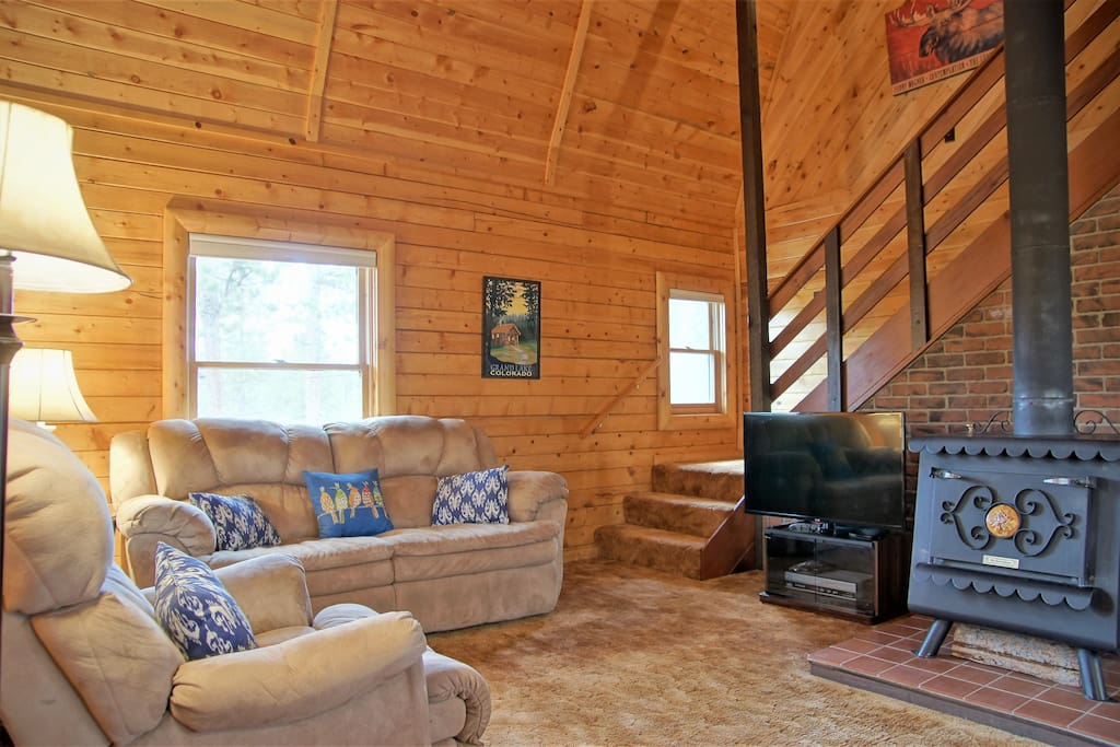 The main living room features vaulted ceilings, nice furniture, HDTV, and Wood Stove