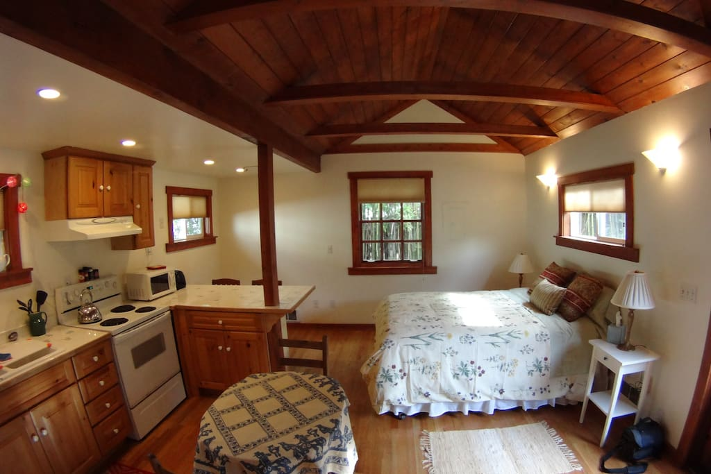 Main room of cabin with queen size bed and small drop leaf table