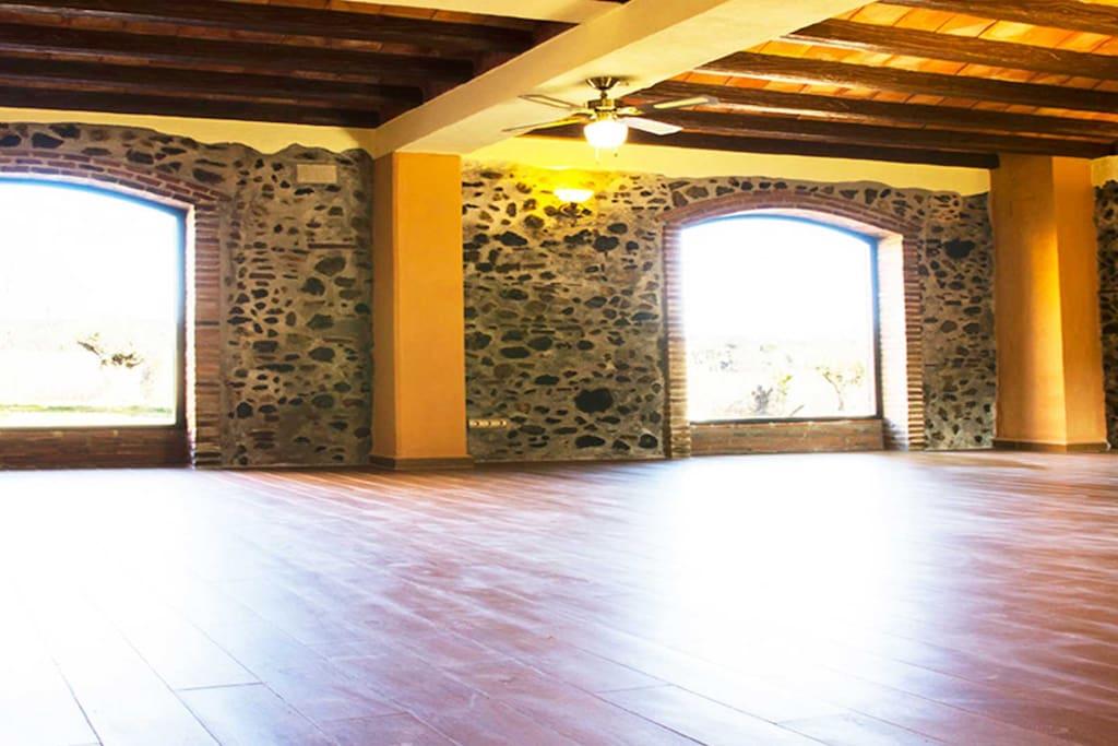 Sala polivalente de 100M2 con ventanales y comunicada con el porche-terraza