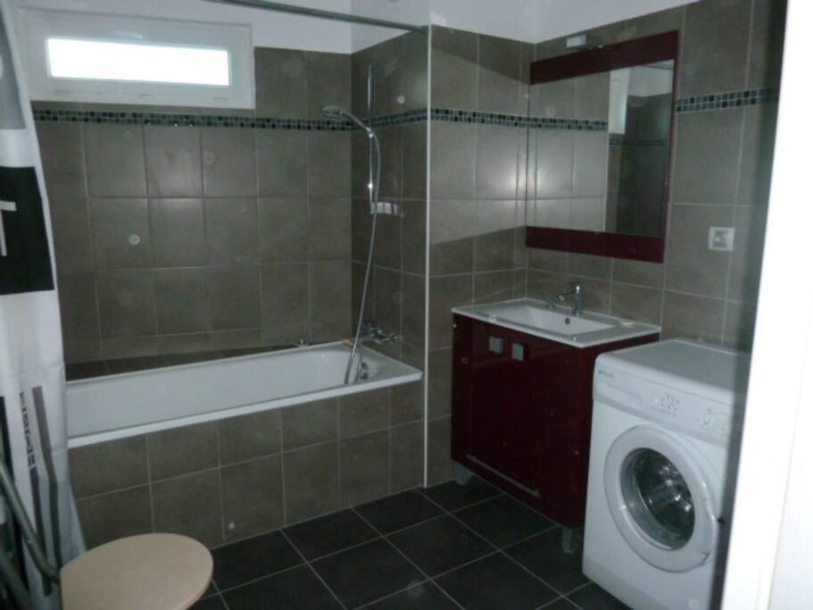 Salle de bain avec baignoire et machine a laver