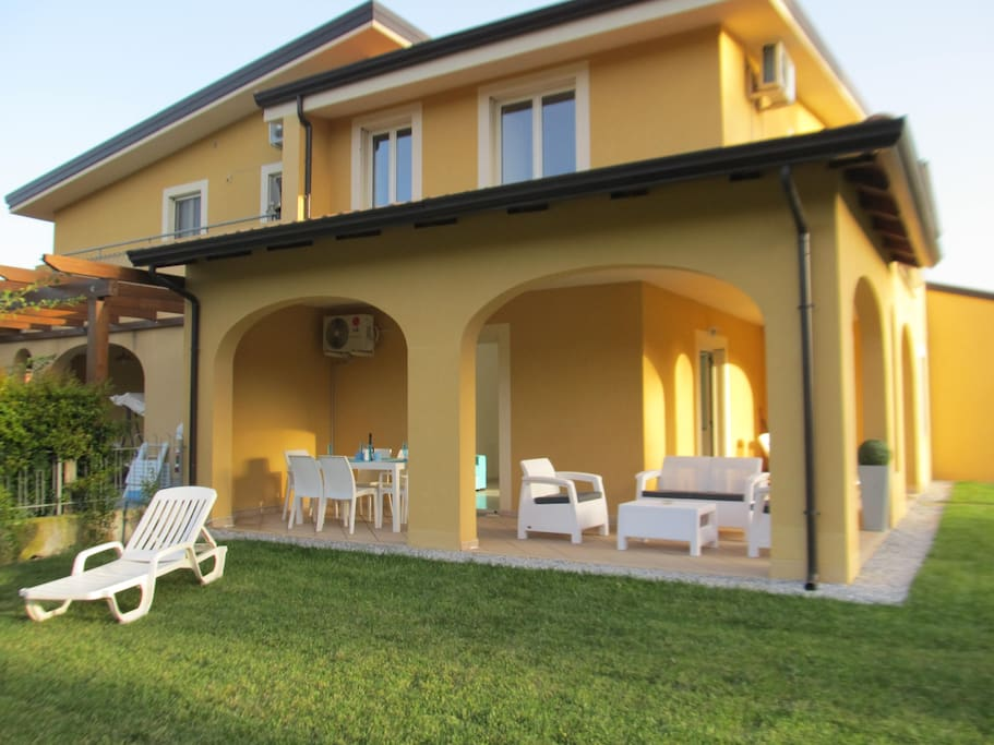 Large landscaped garden with terrace and outdoor furniture.