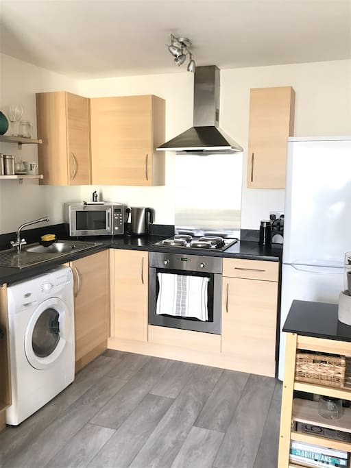 Open plan kitchen with washer/dryer, electric cooker/grill/oven, microwave, fridge/freezer, Nespresso coffee machine, kettle and toaster.