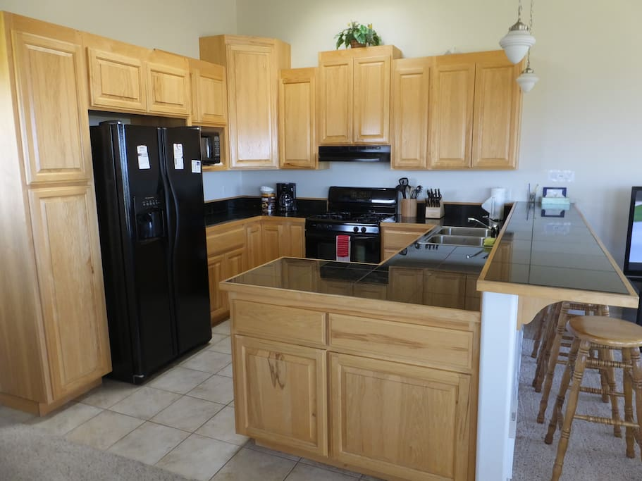 Kitchen is fully equipped with a cooking stove and side by side refrigerator