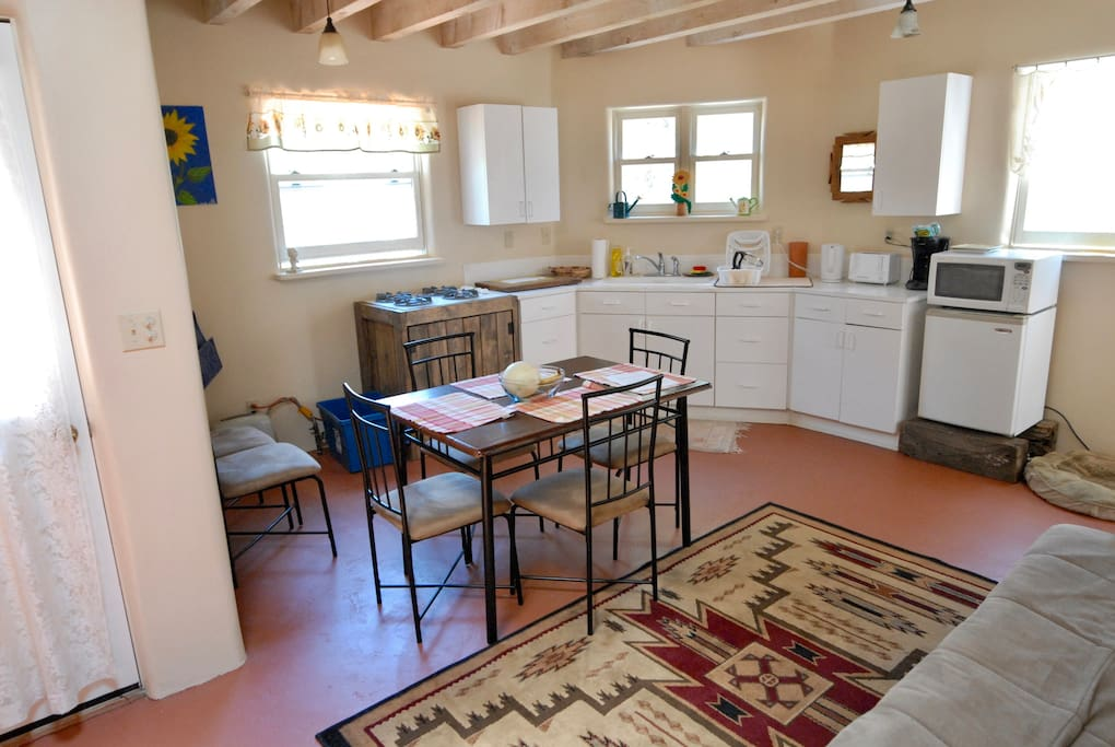 Spacious kitchen with 4 burner gas stove, microwave, toaster, electric kettle and dining table