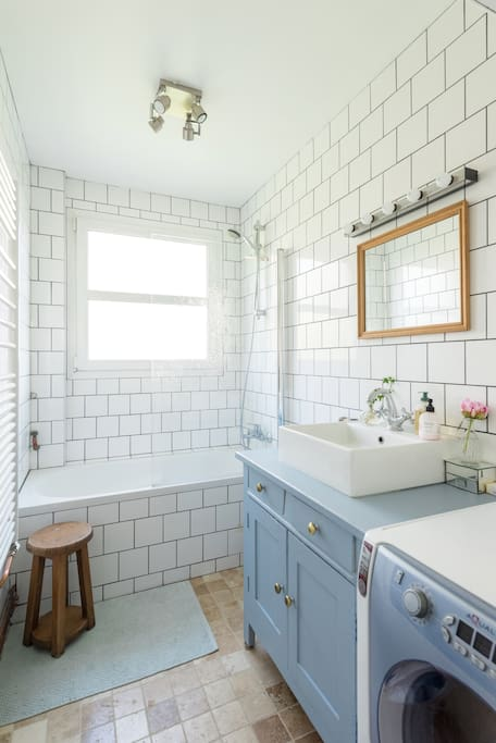 Renovated, tiled bathroom with hot tub and washing machine
