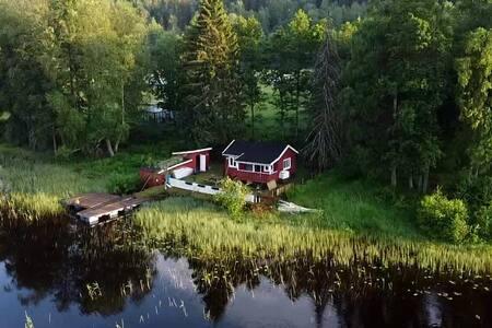 Koselig hytte i vannkanten med brygge og motorbåt