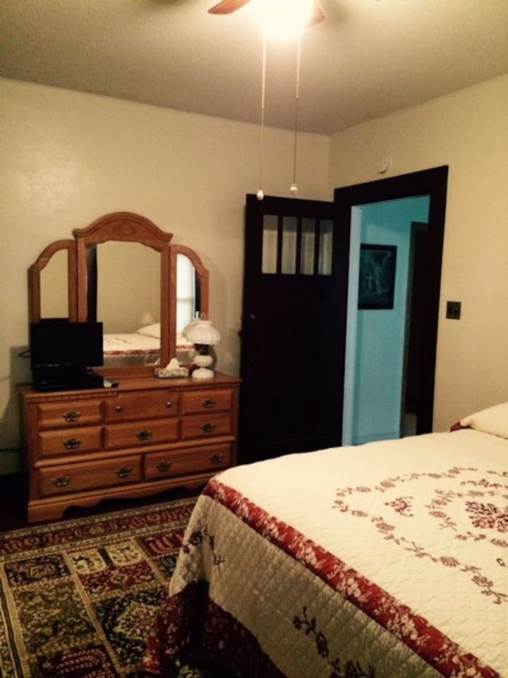 Main floor bedroom with tv, ceiling fan, roomy closet.
