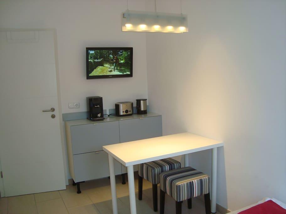 TV, Esstisch und Kaffee-Ecke.