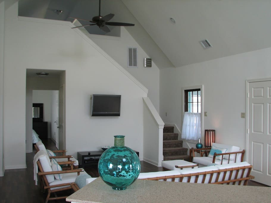 Main living area with wall mounted TV and stairs to loft.