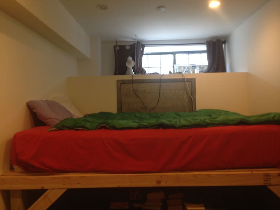Lofted Queen size bed with sheets, blanket and two pillows