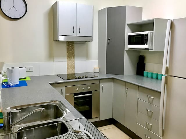 Fully equipped kitchen with dishwasher, 4 burner hotplates, built in oven.