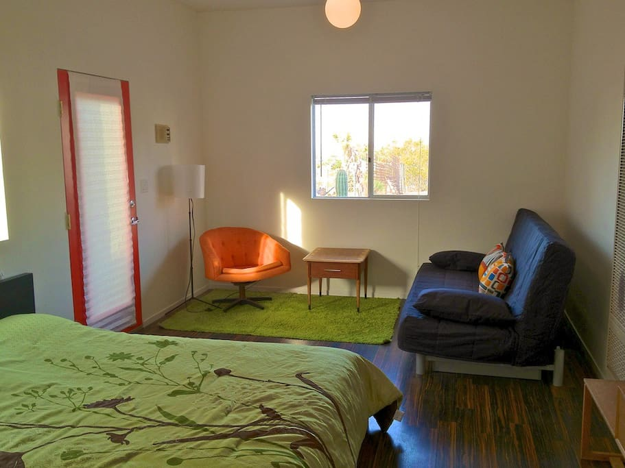 View of entrance door to studio. Queen bed in foreground, sofa bed on right.