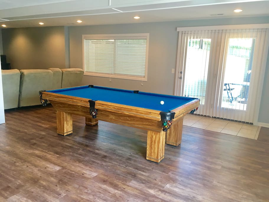 The basement complete with regulation size pool table, couch with recliners built in, a Smart TV, stereo system, and PS4. Walk out patio to private entrance through backyard.