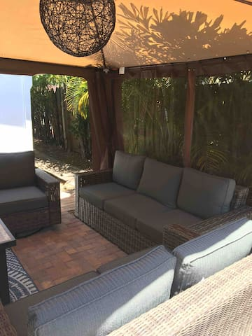 Enclosed fenced gated furnished patio with a fire pit and gas grill .