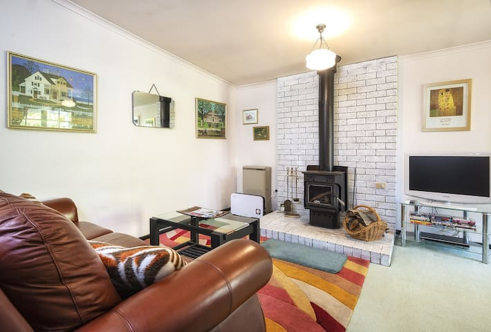 Lounge with large and extremely comfy sofa, gas heating, a Ned Kelly wood burner and a smart TV with Netflix