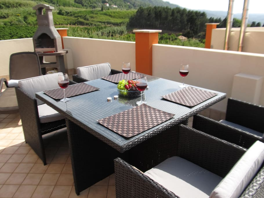 Roof terrace solarium with excellent outdoor furniture and stone brick BBQ