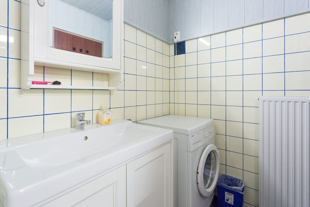 Newly renovated bathroom with washer, vanity table and lots of shelf space for your toiletry
