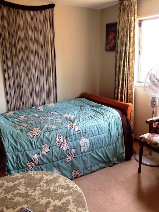 Cama plaza y media con opción de otra cama nido. TV, calefacción y baño compartido con otra habitación, si estuviera ocupada. Vista hermosa al jardín y piscina.