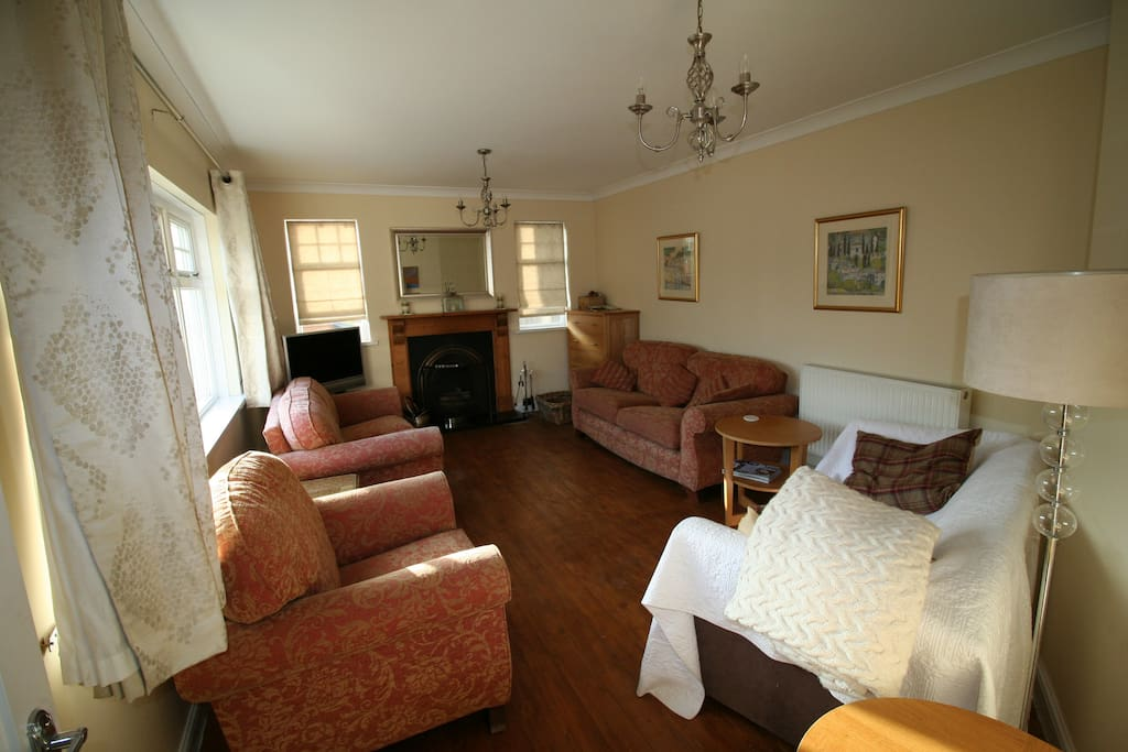 The sitting room, with three comfortable sofas plus armchair, TV and open fire