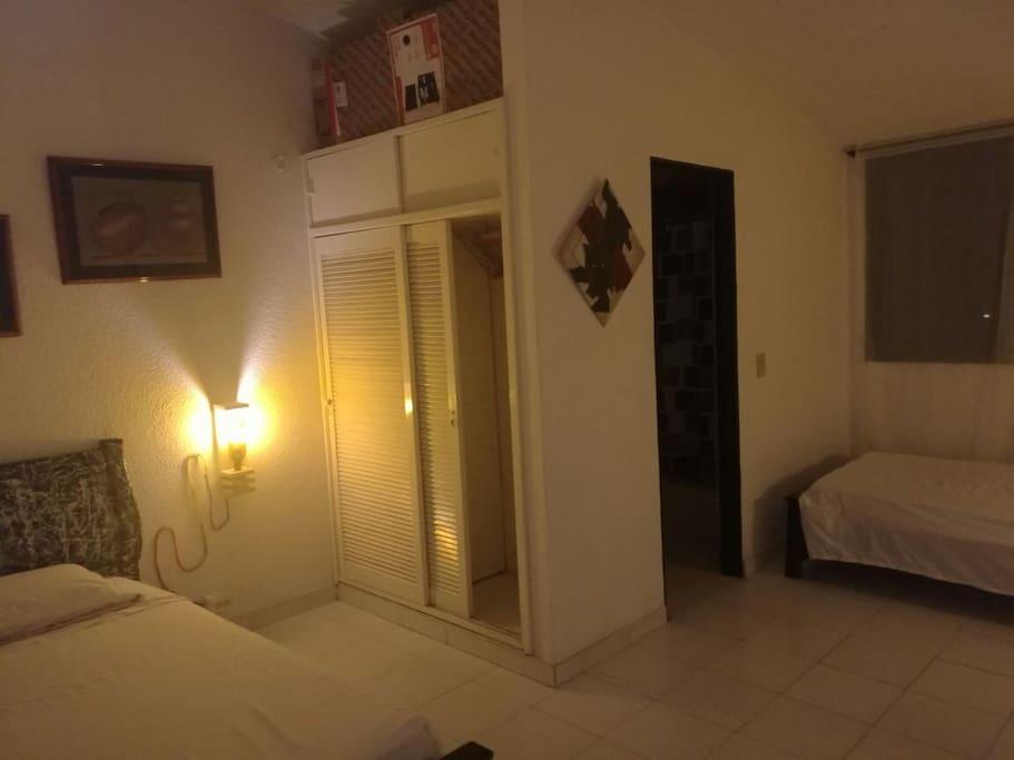 Habitación con dos camas sencillas, baño y closet