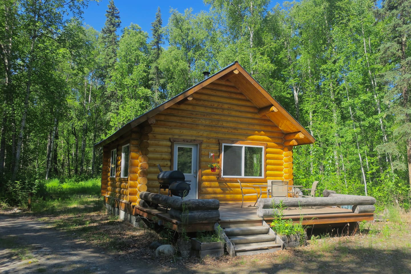 Cozy log cabin nestled in the woods near Christiansen Lake, including large front deck with grill, dining table, and chairs