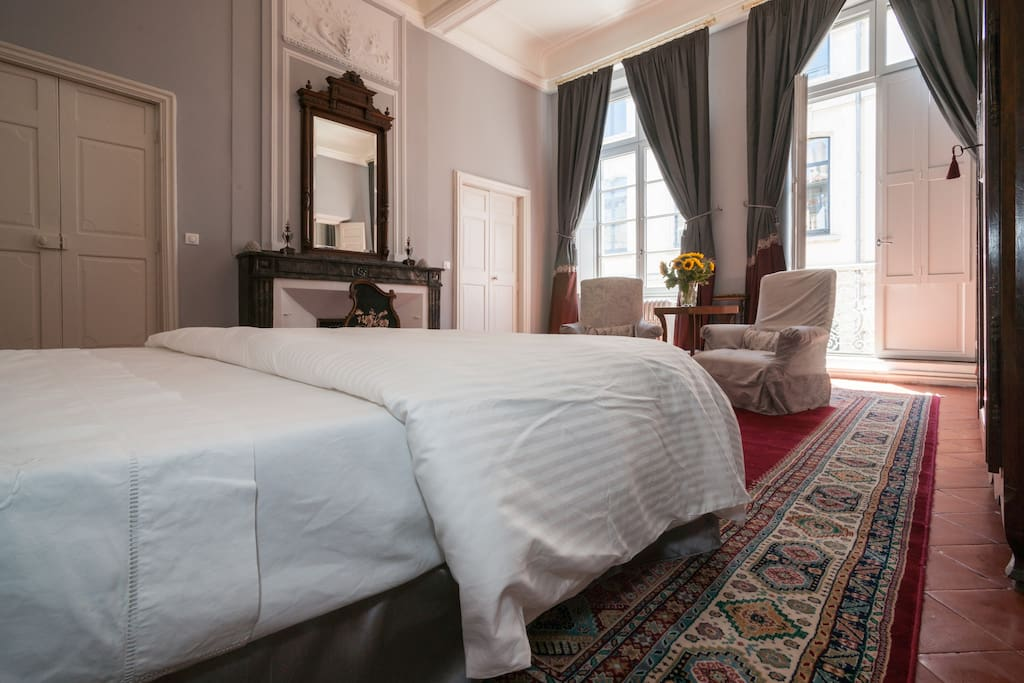Classic French bedroom with light grey walls, traditional furniture, and glorious natural light. #French #bedroomdecor #classicFrench #vacationrental