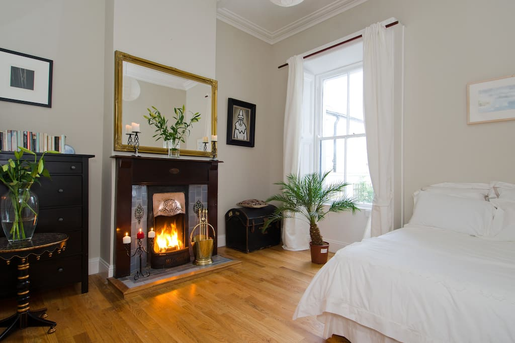 Spacious double bedroom with feature fireplace and high ceilings