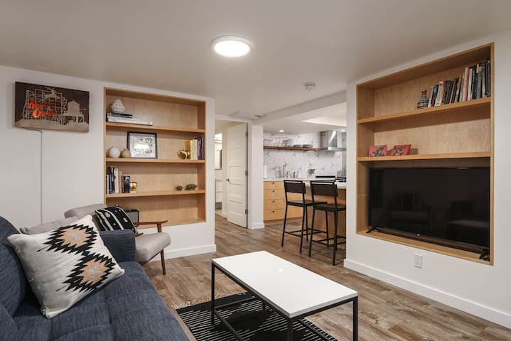 Living room includes built-in shelving with Roku TV, and opens onto kitchen peninsula.