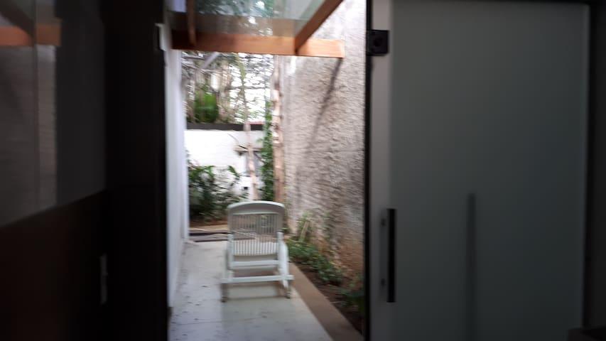 Espaço externo para area de lazer e jardim  com piso de porcelanato.