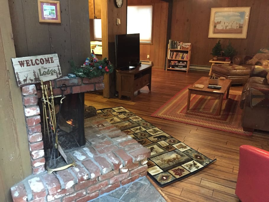 Entrance into living room with wood burning fireplace, flatscreen TV with DVD player, lots of DVD movies, games and books.