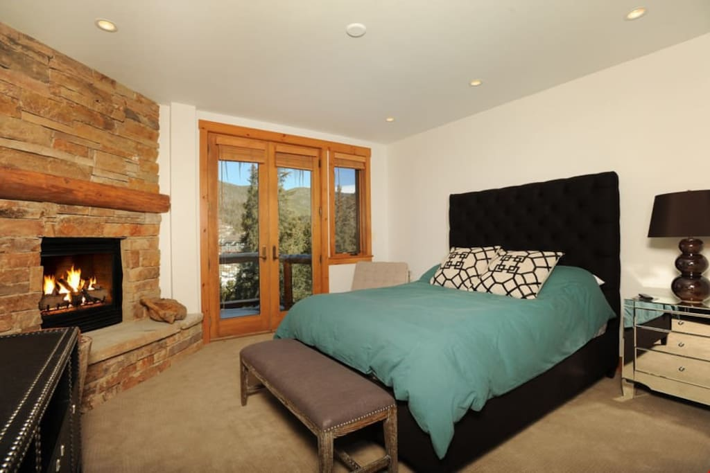 The master bedroom features a queen bed and access to the private balcony