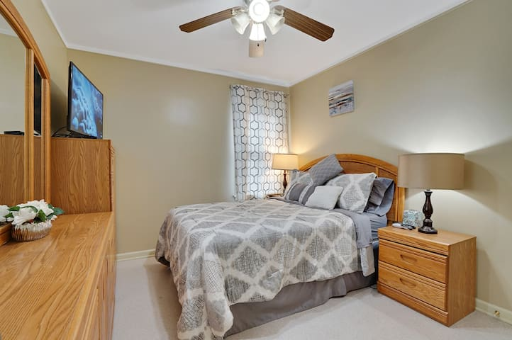 Spacious downstairs cute bedroom with full sized bed, 2 night stands, 2 table lamps, new cute  comforter, additional comfy thin quilt, new big LED Samsung TV, closet, chest, dresser with mirror and ceiling fan