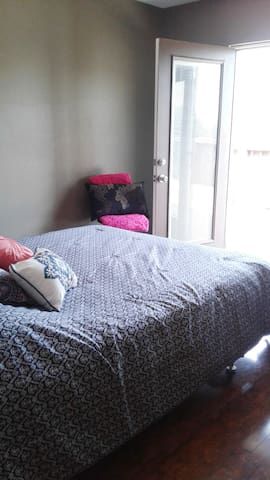 Queen bed with private large balcony overlooking the backyard