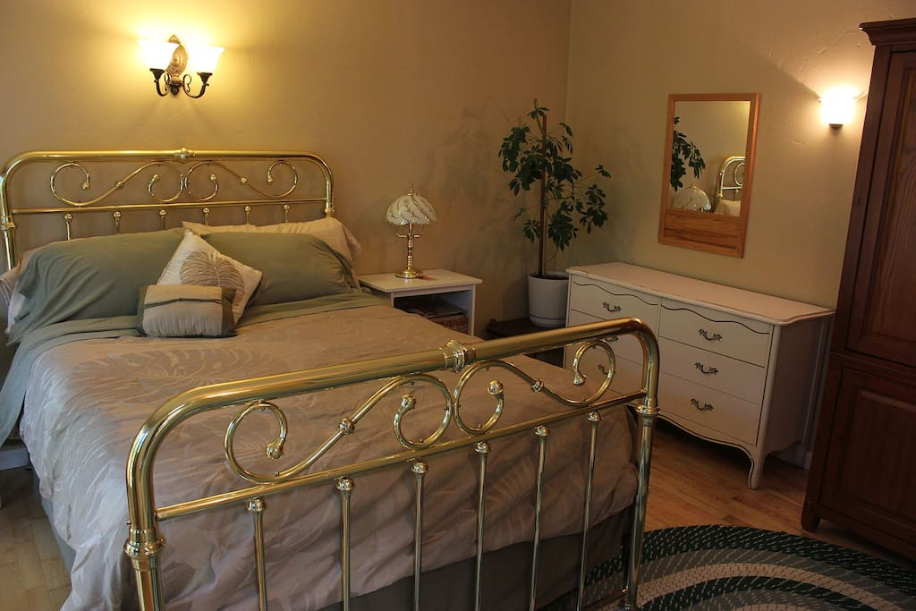 Queen-sized bed with brass frame.