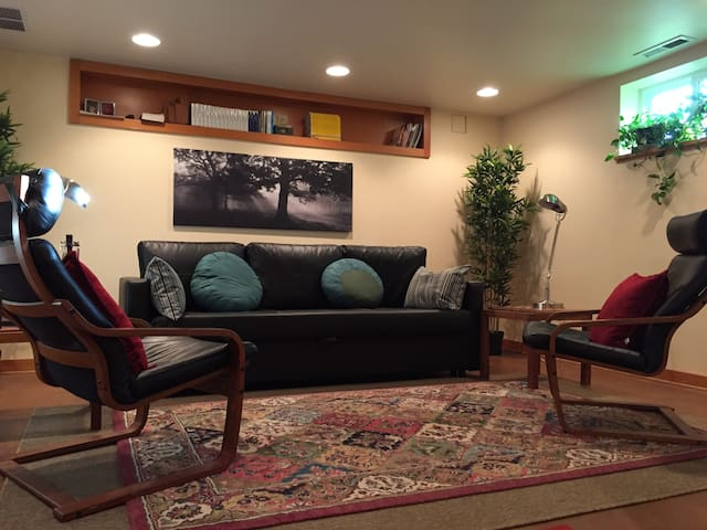 The well appointed living room features a fold-out queen-size bed inside that comfortable faux-leather couch.