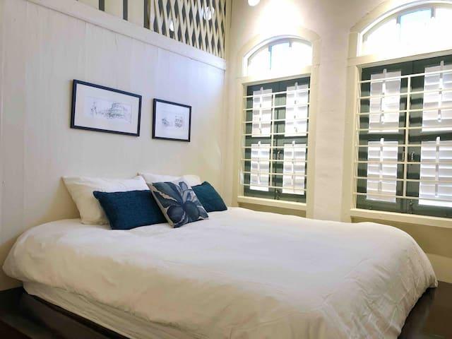 战前老屋,木楼板梁,百叶窗都依然那么的美。 The deluxe bedroom with king size bed has bars on the windows and wooden shutters that can be left open or closed according to the weather.