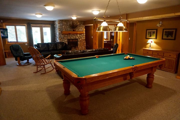 Huge family room in the basement with pool table and fireplace.