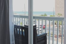 Two large glass doors reveal the balcony overlooking the waves crashing on the beach. Look down and you see the crosswalk from the Kraken directly to the beach.