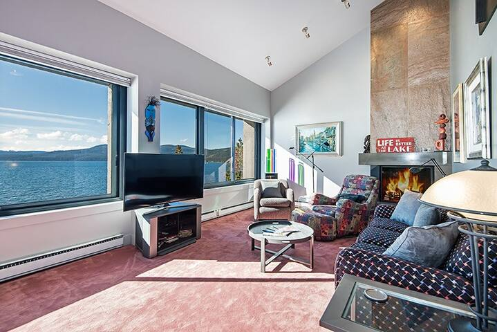"The living room is furnished with a comfy sofa and chairs, a sleek gas fireplace, and 50"" flat screen TV."