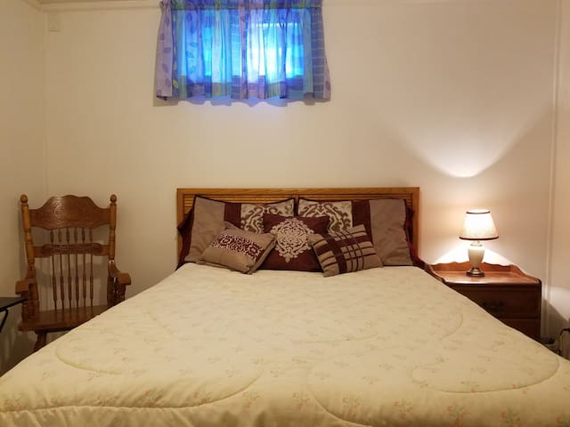 Bedroom with full size bed, night stand, closet, bureau, high back chair with end table.