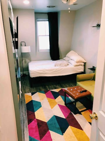The bedroom is furnished with a queen bed, a loveseat, and full length mirror. The curtians are blackout curtains and also dampen the noise from outside. Perfect for getting a good night's sleep. The TV is a smart 50in tv with Netflix, Hulu++