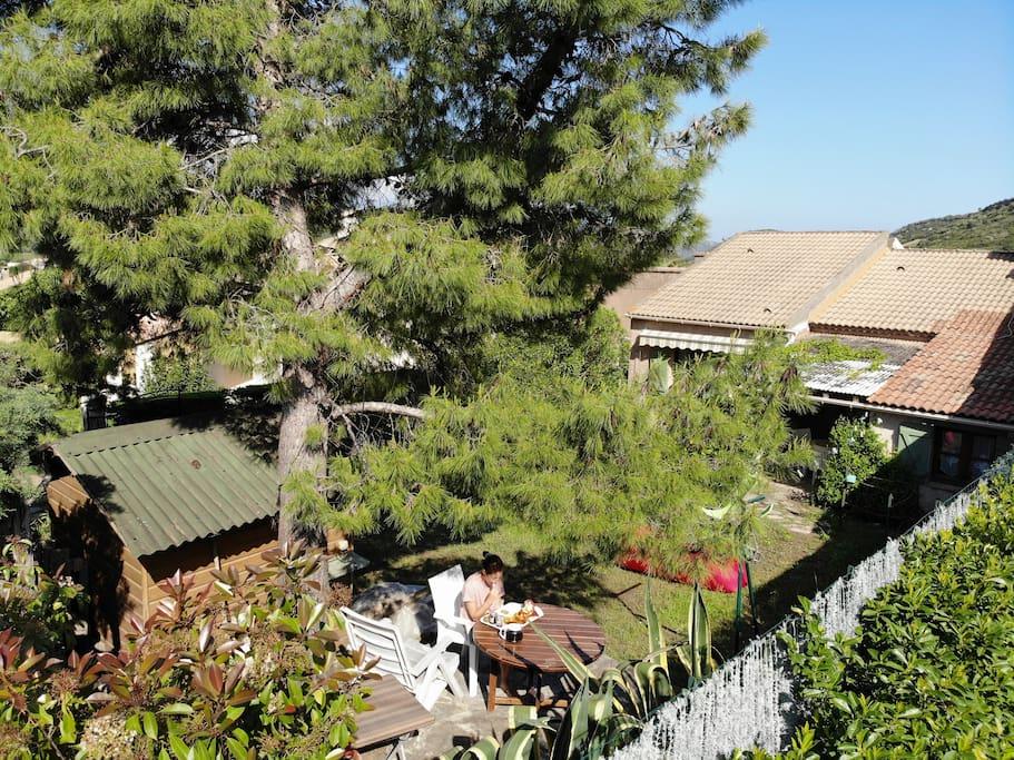 Une petite terrasse en bout de jardin permet de profiter de l'ombre et de l'air en cas de chaleur.