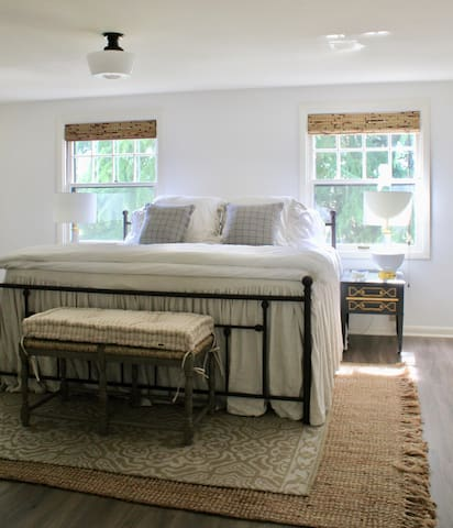 King bed with luxurious linens, walk in closet and writing desk.