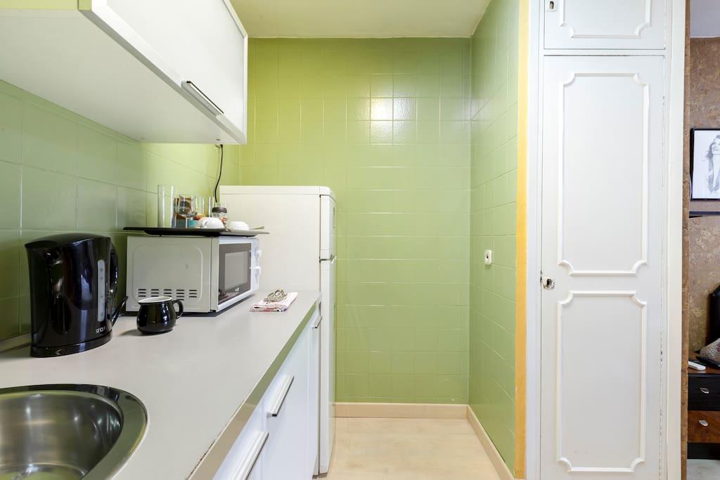 Pequeña cocina con frigorífico, microondas y calentador de agua.